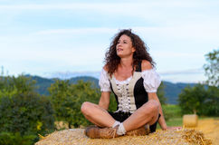 Pretty woman sitting on a hay bale daydreaming. Pretty young woman sitting on a hay bale in a rural farm field looking up into the air with a faraway expression Royalty Free Stock Photography