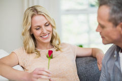 Pretty woman sitting on her couch and husband offering a rose Royalty Free Stock Photos