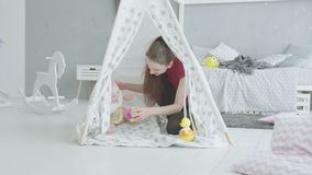 Joyful mother playing with baby in children`s hut stock video