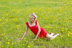 Pretty woman sitting on a meadow Royalty Free Stock Image