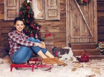 Pretty woman sitting near the Christmas tree Stock Photos