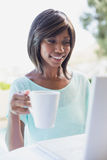 Pretty woman sitting outside using laptop having coffee Royalty Free Stock Photos