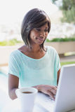 Pretty woman sitting outside using laptop. On a sunny day Royalty Free Stock Photo