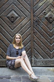 Pretty woman sitting on the pavement outside an ancient wooden door. Stock Photo