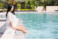 Pretty woman sitting by the pool Stock Images