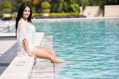 Pretty woman sitting by the pool Royalty Free Stock Photography