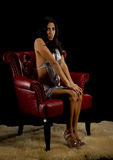 Pretty woman sitting properly in chair. Isolated on a black background, a beautiful young ethnic woman sits properly with her knee's to gether and hands crossed Royalty Free Stock Images