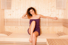 Pretty woman sitting relaxed in a wooden sauna Stock Photo