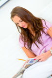Pretty woman sitting on sofa and doing crosswords Stock Photos