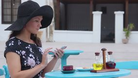 Pretty woman sitting at street cafe, typing message on smartphone, smiling. Stock footage stock video footage