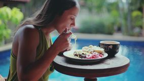 Pretty woman sitting on the terrace by pool on the tropical villa resort and enjoying dinner, exotic summer vacation. Pretty woman sitting on the terrace on the stock video