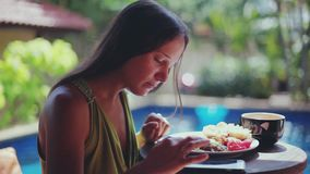 Pretty woman sitting on the terrace on the tropical villa resort and enjoying breakfast and uses mobile phone, exotic. Pretty woman sitting on the terrace on the stock footage