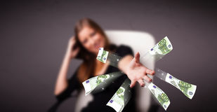 Pretty woman sitting and throwing money Royalty Free Stock Images