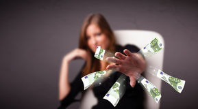 Pretty woman sitting and throwing money Royalty Free Stock Photos