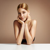 Pretty woman sitting and touching her face Royalty Free Stock Photography