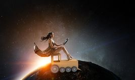 Always like a child. Mixed media. Pretty woman sitting on toy train with steering wheel in hands. Elements of this image are furnished by NASA royalty free stock photo