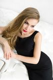 Pretty woman sitting on white leather couch Stock Photo