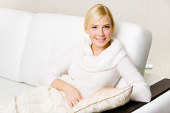Pretty woman sitting on the white sofa. Woman in white sweater sitting on the sofa with the pillow under her hand Stock Images
