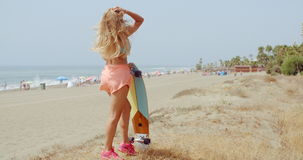 Pretty Woman with Skateboard Posing at the Beach stock video