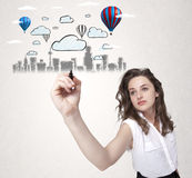 Pretty woman sketching cityscape with colorful balloons Royalty Free Stock Image