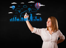 Pretty woman sketching cityscape with colorful balloons Stock Photos