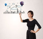 Pretty woman sketching cityscape with colorful balloons Royalty Free Stock Photography