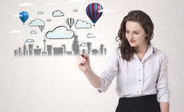 Pretty woman sketching cityscape with colorful balloons Royalty Free Stock Photos