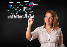 Pretty woman sketching cityscape with colorful balloons Royalty Free Stock Photo