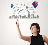 Pretty woman sketching cityscape with colorful balloons Stock Images