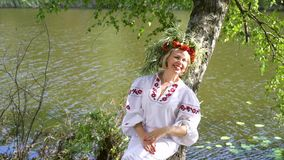 Pretty woman in slavic traditional costume lying on trunk of birch tree. Pretty woman in slavic traditional dress and floral circlet lying on trunk of birch tree stock footage