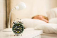 Pretty woman sleeping with alarm clock view Stock Photos