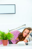 Pretty woman sleeping on divan at home. In front of TV with remote control on table Royalty Free Stock Photography