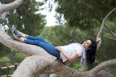 Pretty woman sleeping in a tree after being over worked and having trouble sleeping Royalty Free Stock Photography