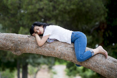 Pretty woman sleeping in a tree after being over worked and having trouble sleeping Stock Image