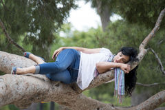 Pretty woman sleeping in a tree after being over worked and having trouble sleeping Stock Images