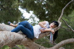 Pretty woman sleeping in a tree after being over worked and having trouble sleeping Royalty Free Stock Images
