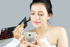 Pretty woman with a smartphone doing makeup Stock Image