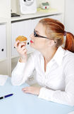 Pretty woman smelling a cupcake in the office. Royalty Free Stock Photos