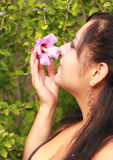 Pretty Woman Smelling Flower. Pretty woman holding and smelling a pink flower Royalty Free Stock Image