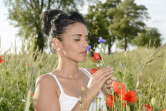 Pretty woman smelling poppy Royalty Free Stock Photography