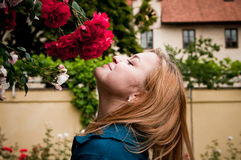 Pretty woman smelling roses Stock Photography