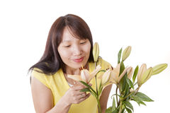 Pretty woman smells lilies. Stock Photo