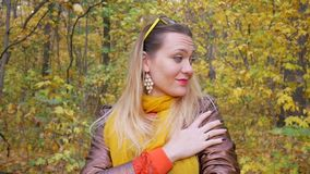 Pretty Woman Smiles in Forest in Autumn. Pretty woman smiles in forest or park on background of trees with yellow leaves in autumn. Female in brown leather stock footage