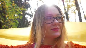 Pretty Woman Smiles in Rays of Sunlight in Forest in Autumn. Pretty woman in yellow glasses smiles in forest or park on background of trees with yellow foliage stock footage