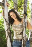 Pretty woman smiling. Portrait of pretty young adult Caucasian brunette woman leaning against tree smiling and looking at viewer Stock Photography