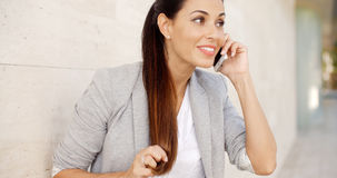 Pretty woman smiling as she chats on a mobile Stock Photography
