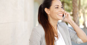 Pretty woman smiling as she chats on a mobile Royalty Free Stock Image