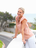 Pretty woman smiling while in the balcony Stock Image