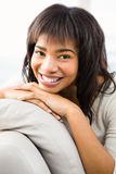 Pretty woman smiling at camera. At home in the living room Royalty Free Stock Image