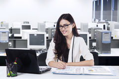 Pretty woman smiling at camera in office Royalty Free Stock Images